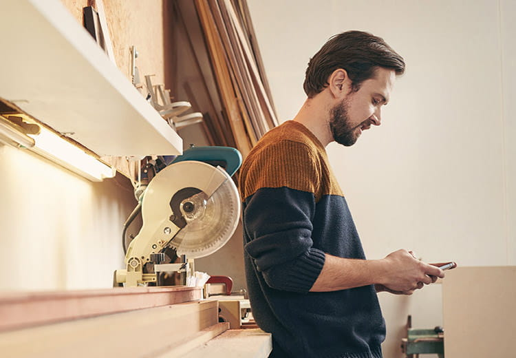 Man in two-tone shirt on his phone in a workshop