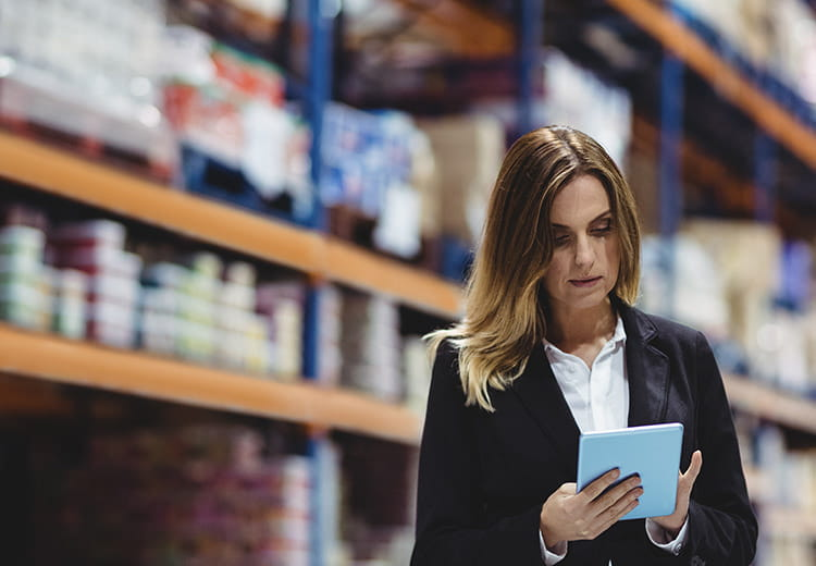 Woman in blazer working on her tablet in warehouse