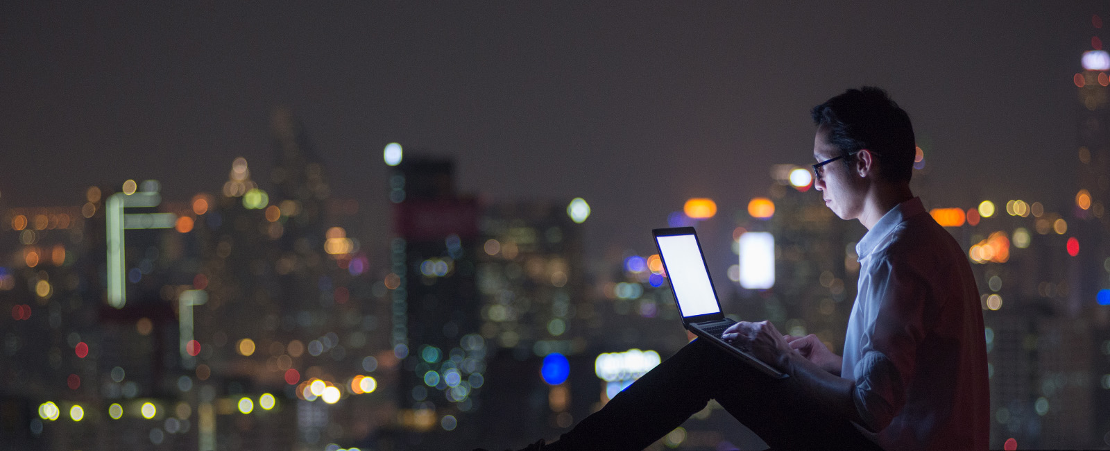 Wide shot of man on his laptop at night with city skyline in background