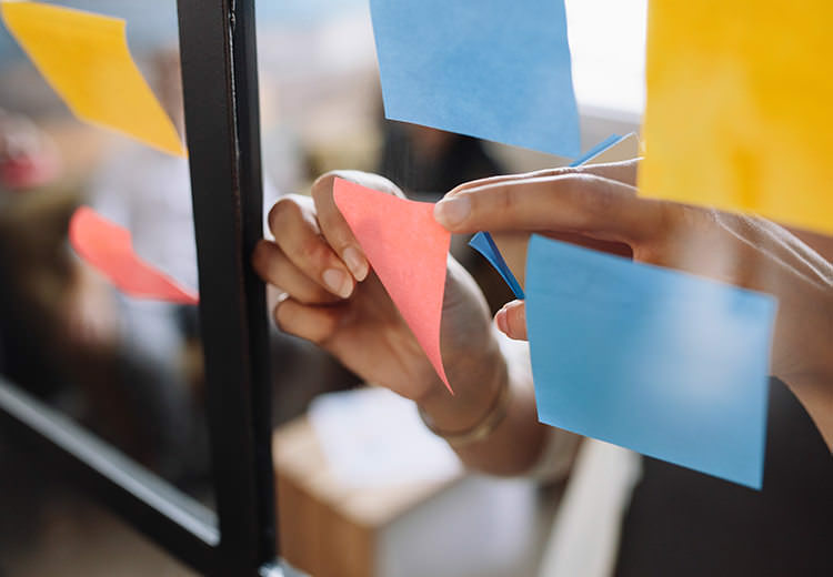 Closup of post-it notes getting put on a glass wall
