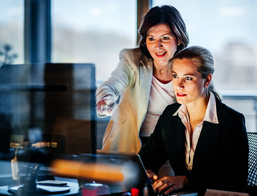 Two female executives look at a computer monitor to review the SAP Ariba Intelligent Spend Management solution