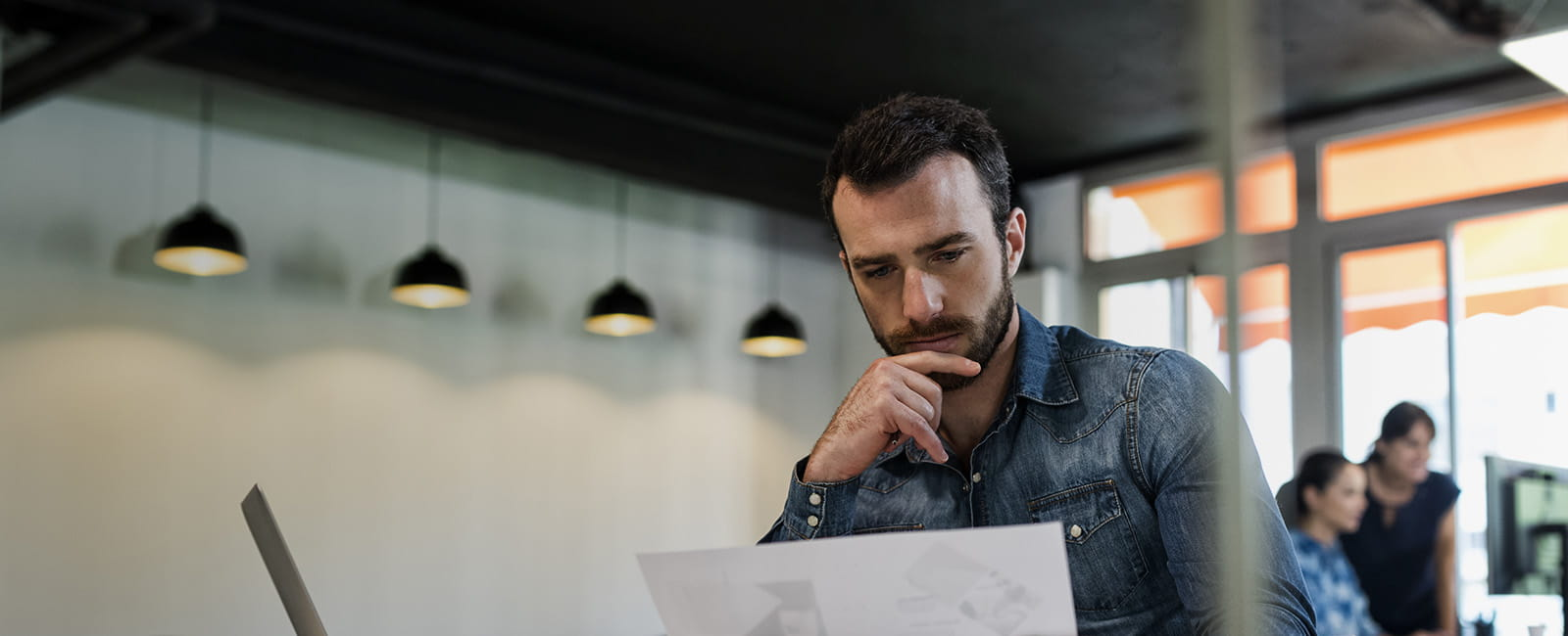 Wide shot of man in a collared shirt looking at paperwork