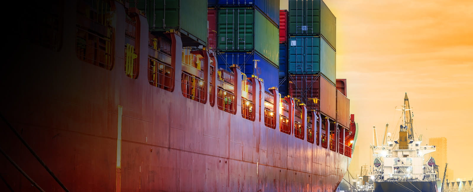 A fully loaded container ship at the dock at sunset