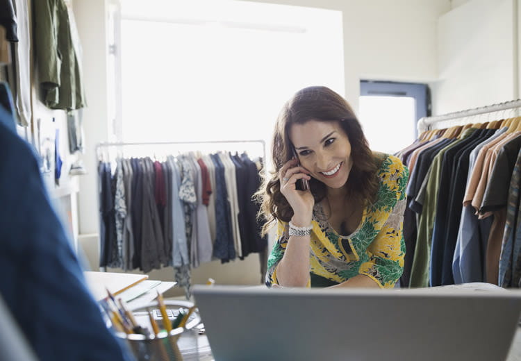 Fashion retailer on a smartphone smiles while reviewing SAP Ariba solutions on a laptop