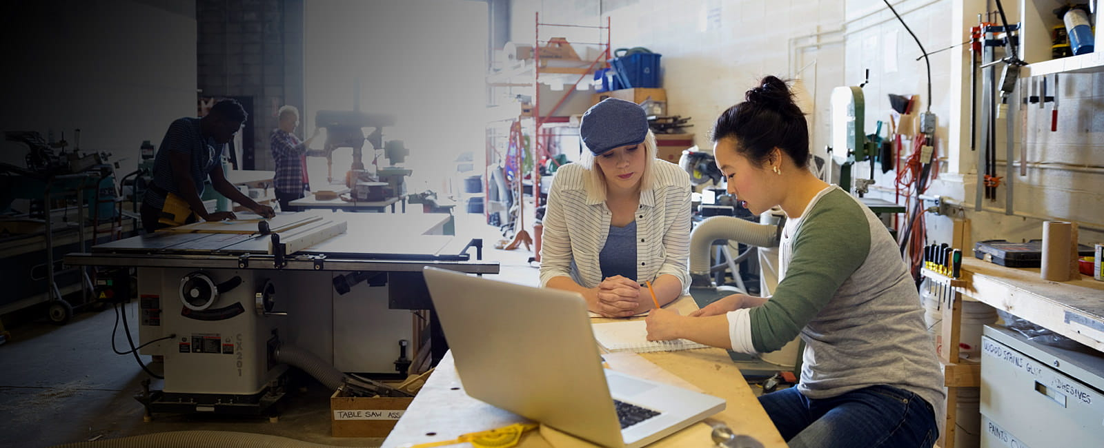 Two women business owners work on a laptop in a manufacturing warehouse