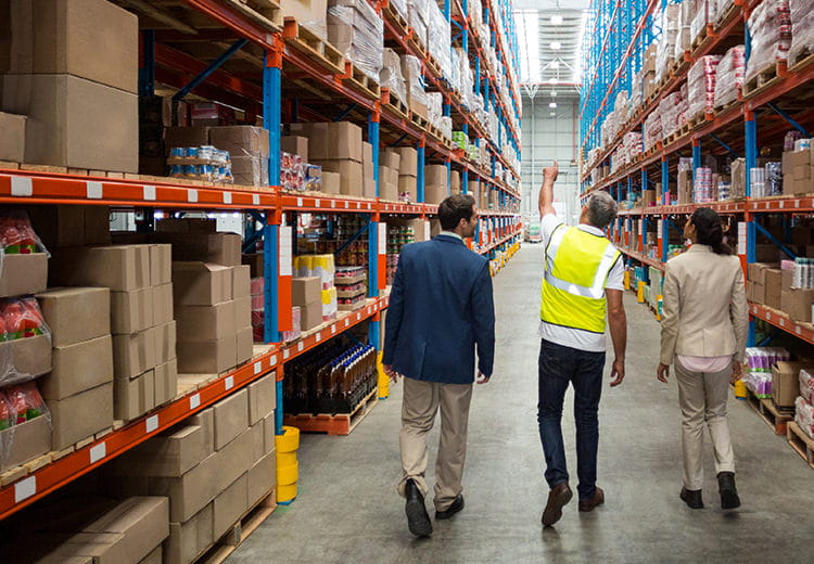 Worker taking people through aisle in warehouse