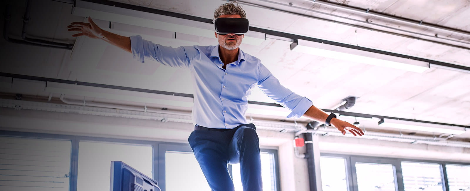 Executive with VR goggles balances on top of an office desk